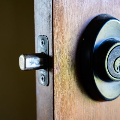 Deadbolt on wooden door engaged with bolt extended